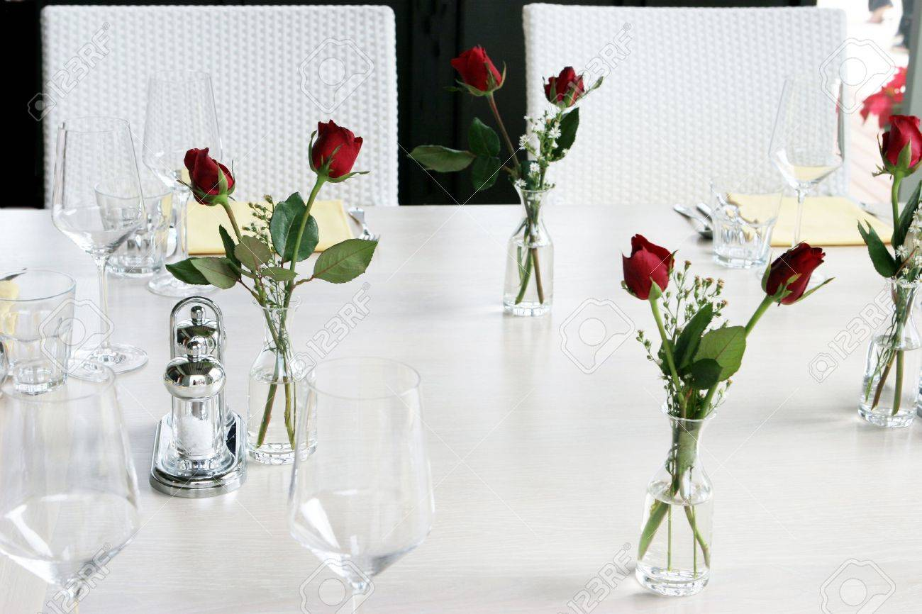 elegant table setting with vases of red roses and white linen
