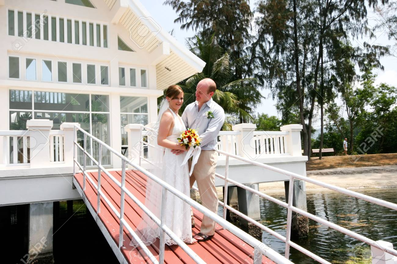 Happy bride and groom outside a wedding chapel. Stock Photo - 4444899