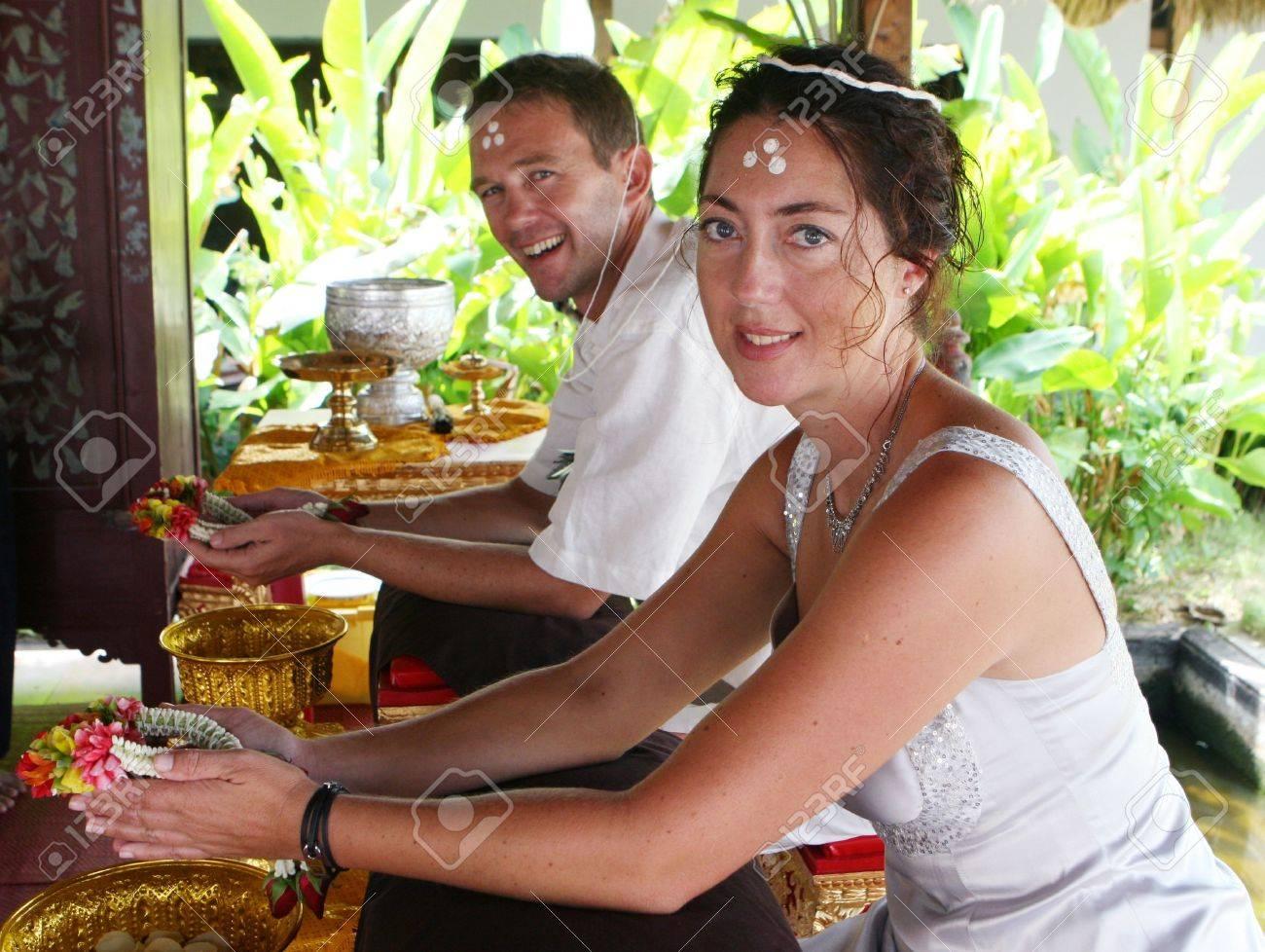 Foto de archivo , Occidental joven matrimonio durante una boda tradicional budista en Tailandia.