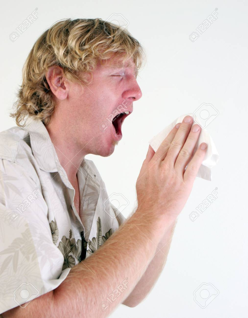 Young man with a cold or flu sneezing - isolated. Stock Photo - 5899695