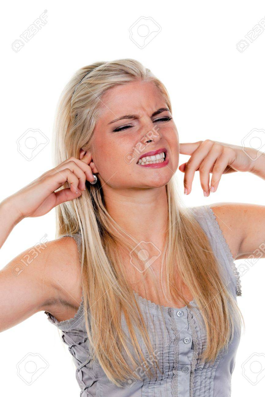 A young woman plugging her ears and grimacing. Vertically framed shot. - 5945467