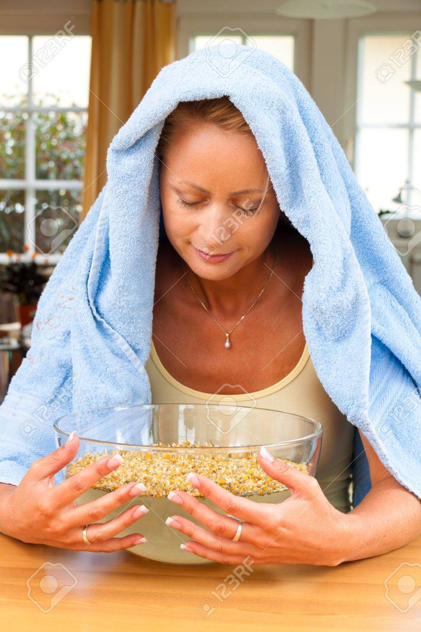 A young woman with colds and flu. Inhalation of herbs. - 7856634