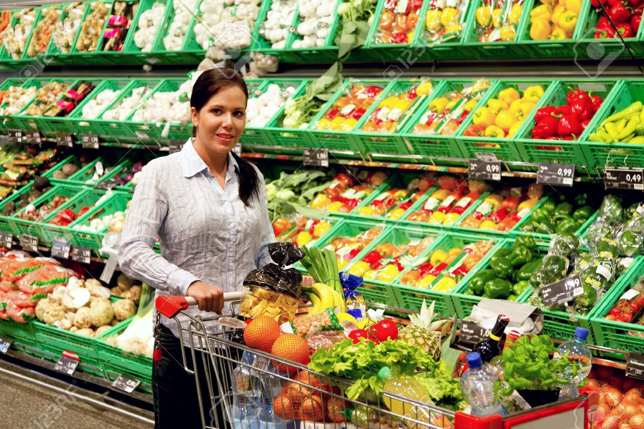 Young woman buys in the supermarket food and fruit. Stock Photo - 8007504
