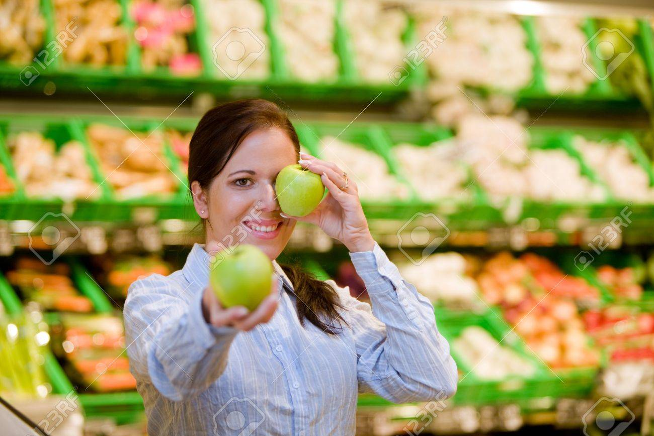 Young woman buys in the supermarket food and fruit. Stock Photo - 8007474