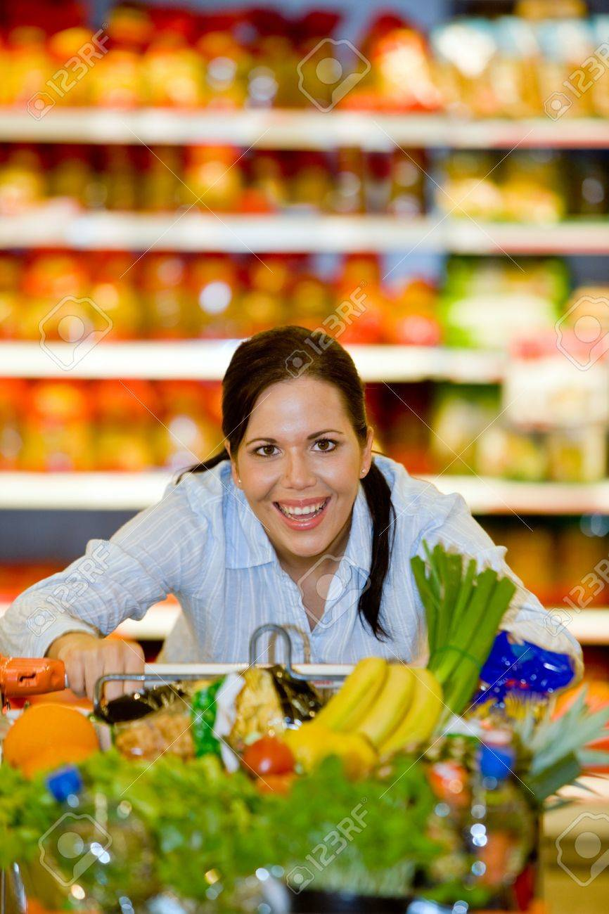 Young woman with shopping cart in the supermarket when shopping. Stock Photo - 8007480