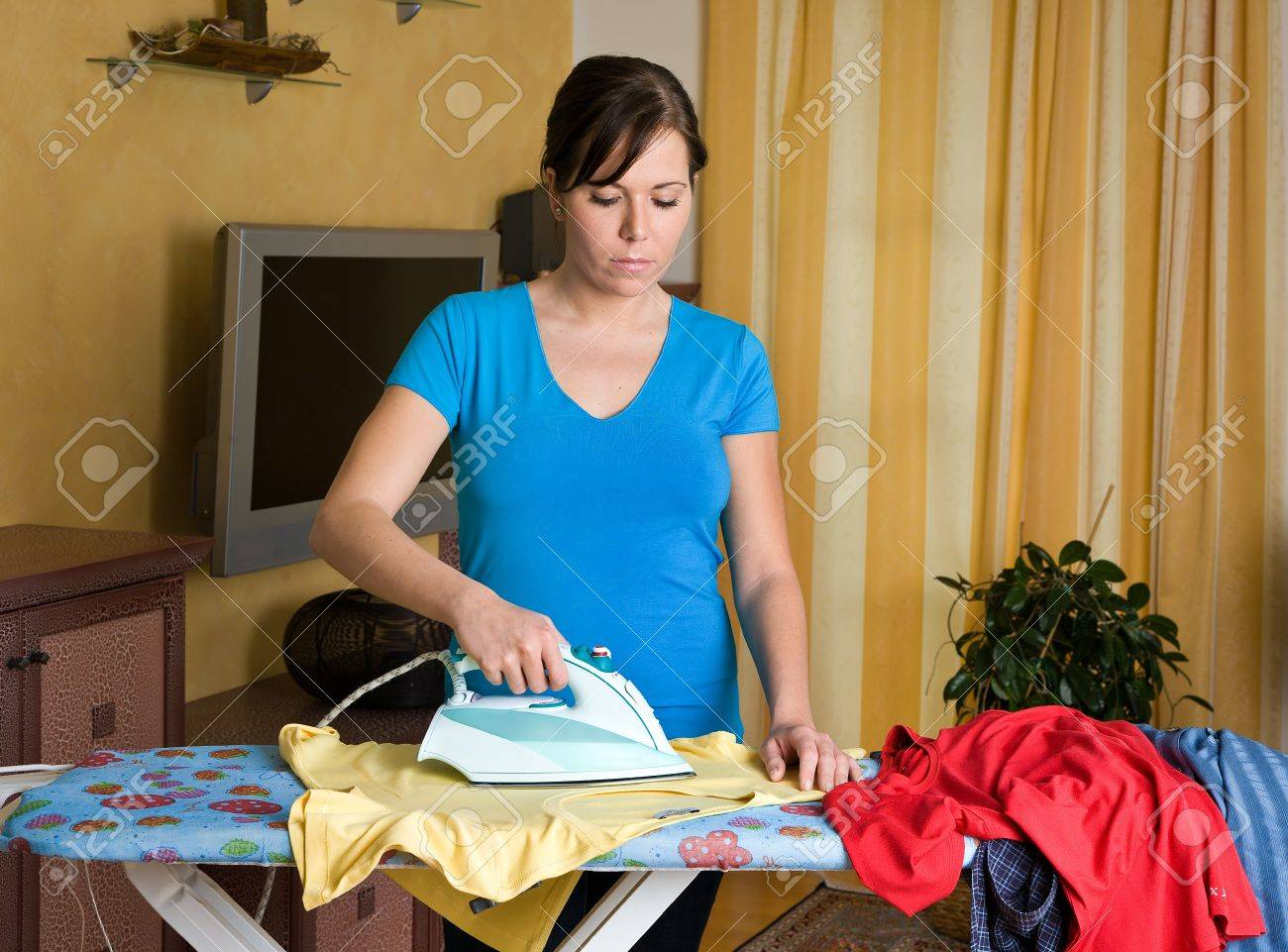 Young Housewife Gets Bored With The Housework. Iron And Ironing ...