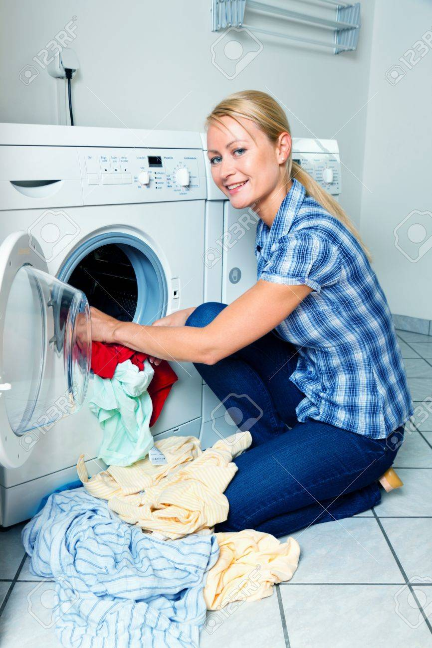 A young housewife with washing machine and clothes. Washing day. Stock Photo - 9307776