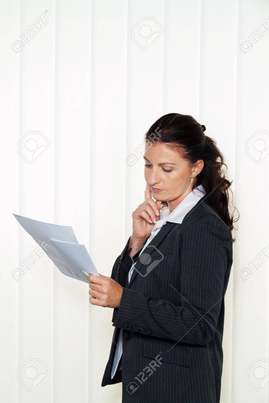 Businesswoman reading a letter in the office message from the businesswoman reading a letter in the office message from the attorney or tax office spiritdancerdesigns Images