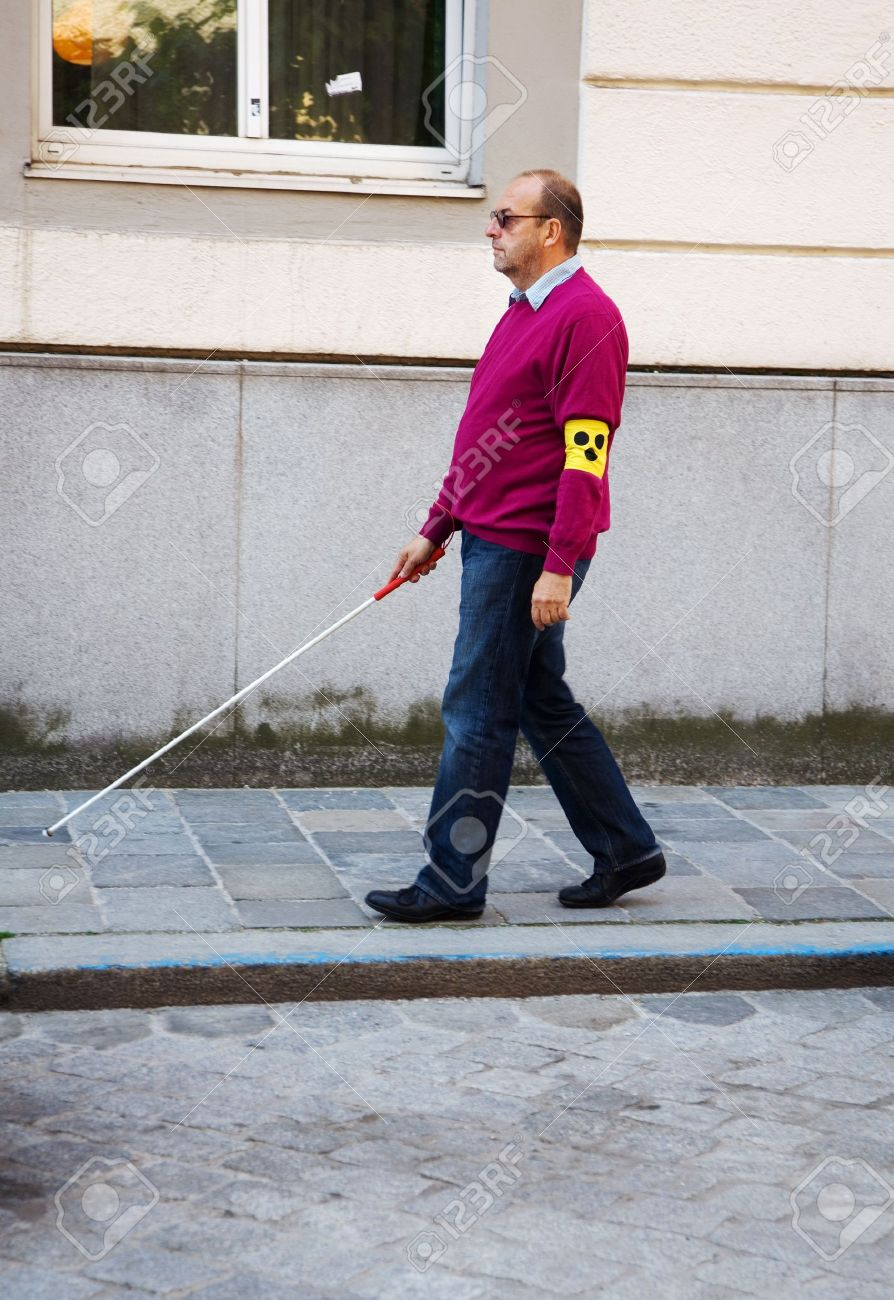 A blind man walks with a cane on a street Stock Photo - 9744870