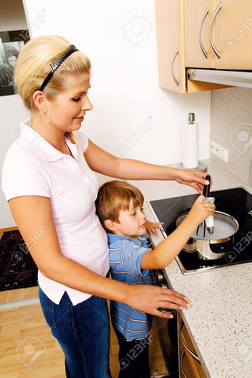 a woman in the kitchen while cooking with electric stove Stock Photo - 11103893