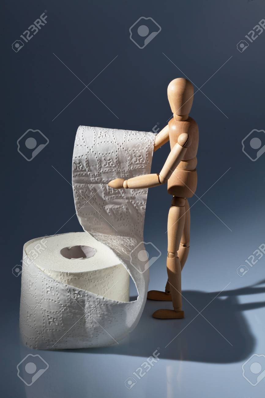 a wooden figure and a roll of toilet paper. Stock Photo - 11275434