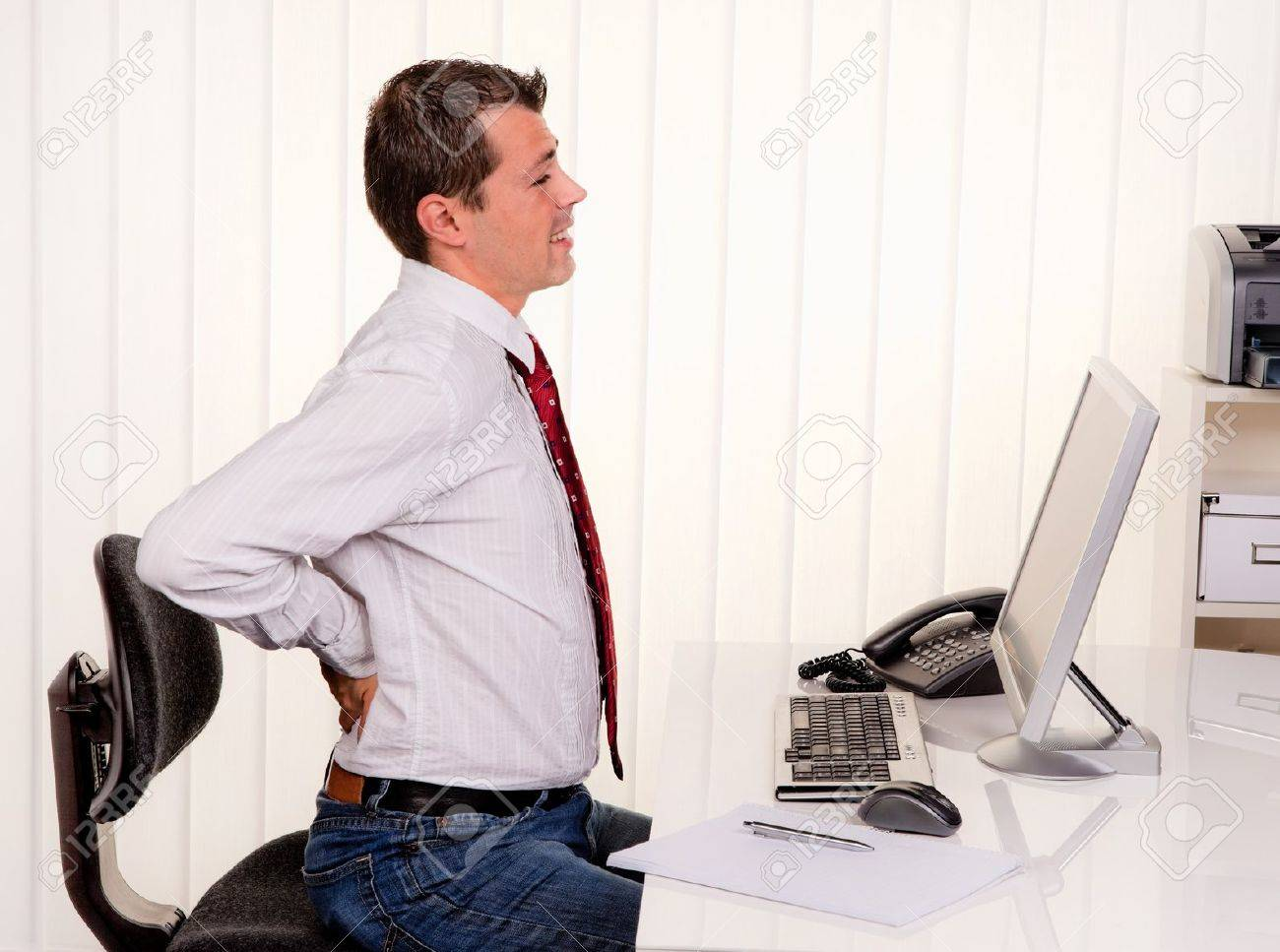 young man in office with computer and back pain Stock Photo - 12080673