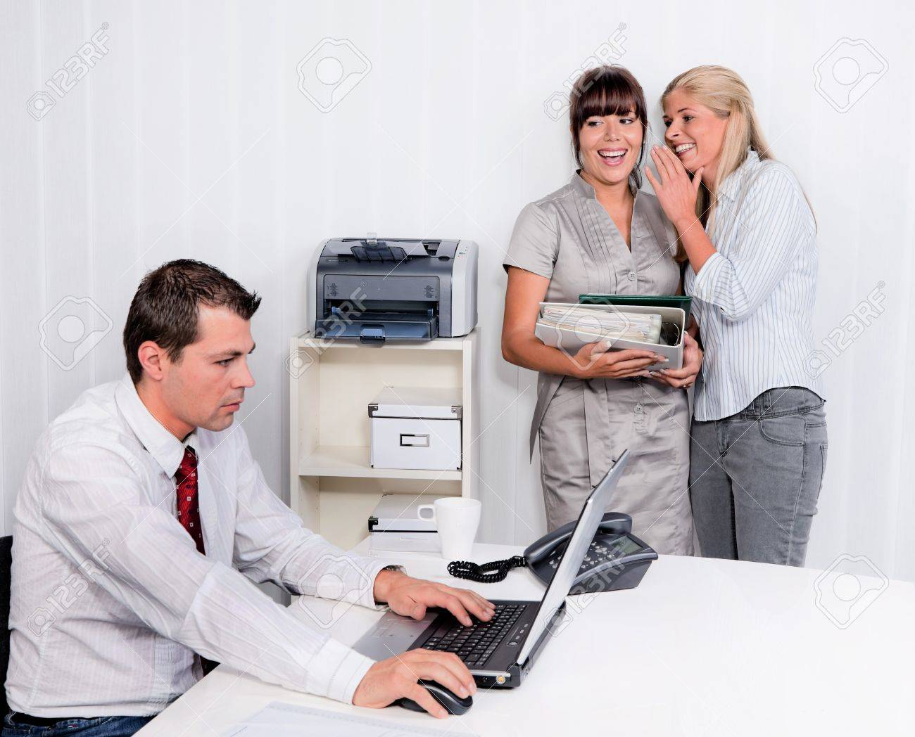 bullying in the workplace an office. two laugh about colleagues Stock Photo - 12080672