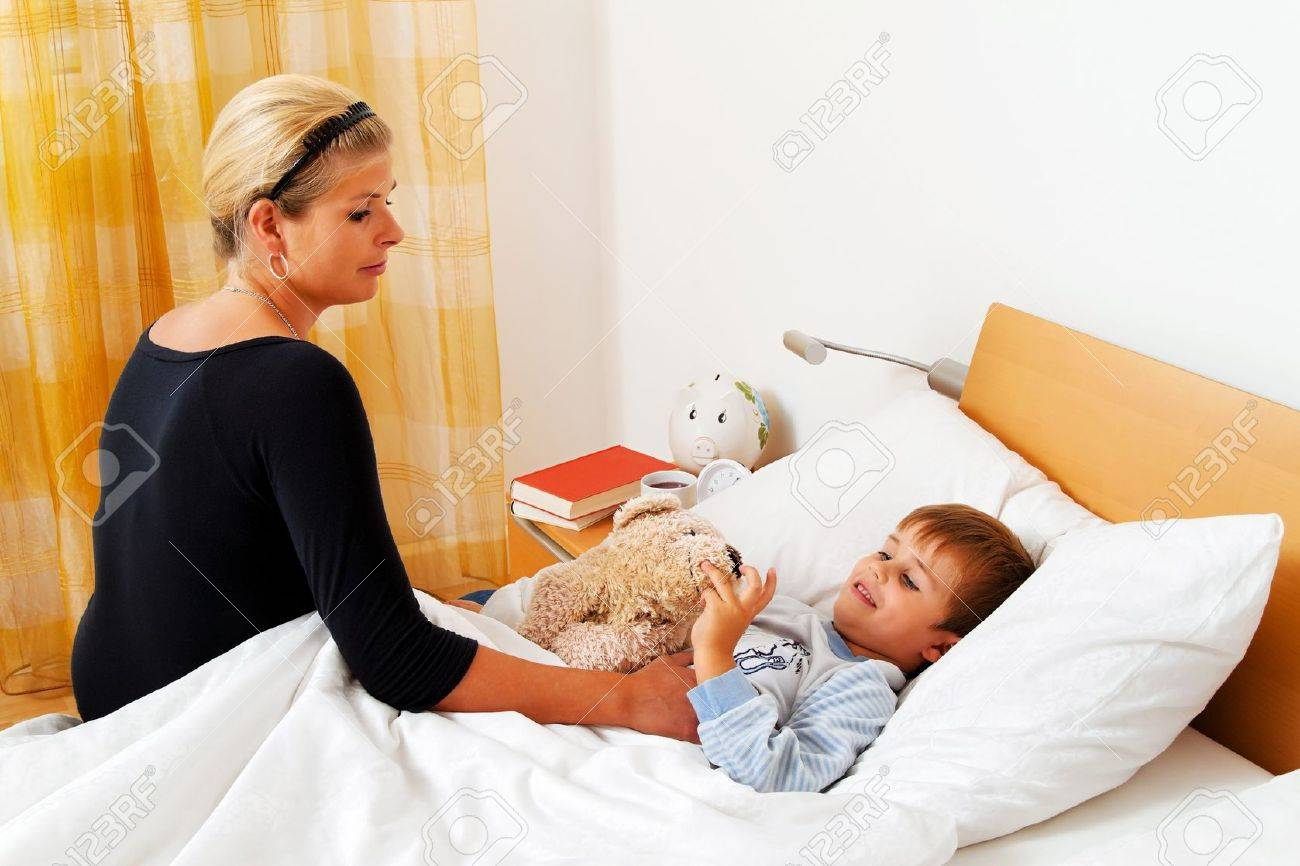 a mother and sick child in bed. influenza. childhood diseases. Stock Photo - 12080667