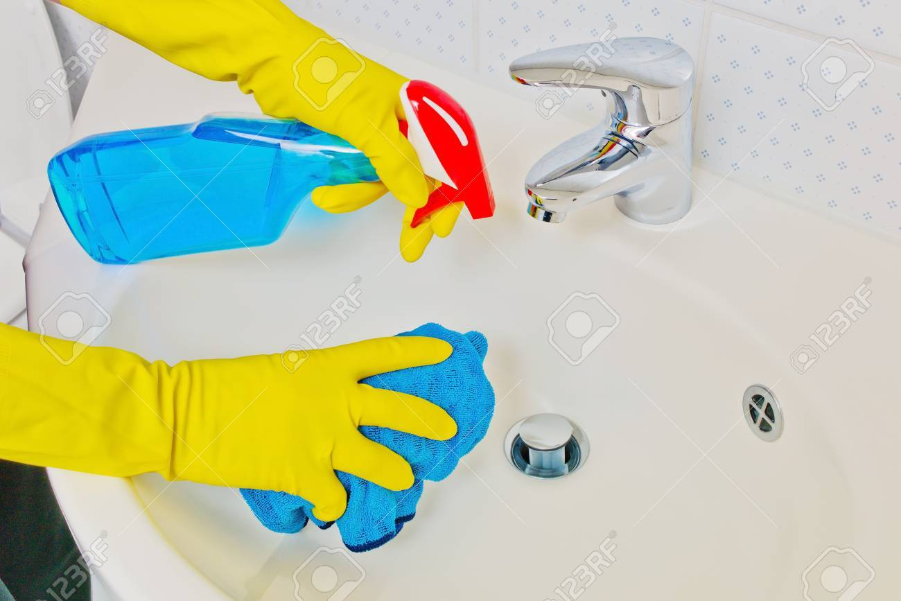 the sink of a bathroom is cleaned with latex gloves Stock Photo - 13776714