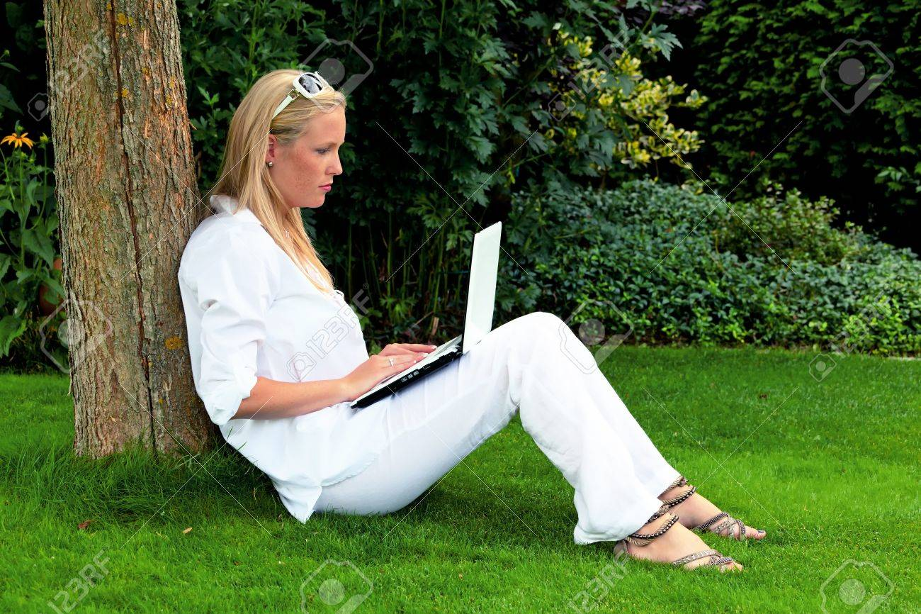 Exceptional A Young Woman Sitting With A Laptop Computer In The Garden And Surf The  Internet Wi