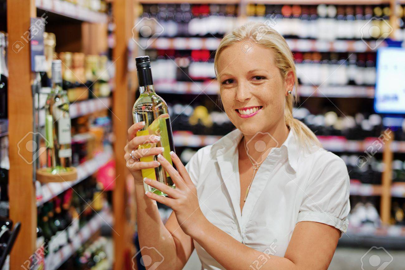 a woman buys wine in a supermarket  wine shelf with wines from around the world Stock Photo - 15652514