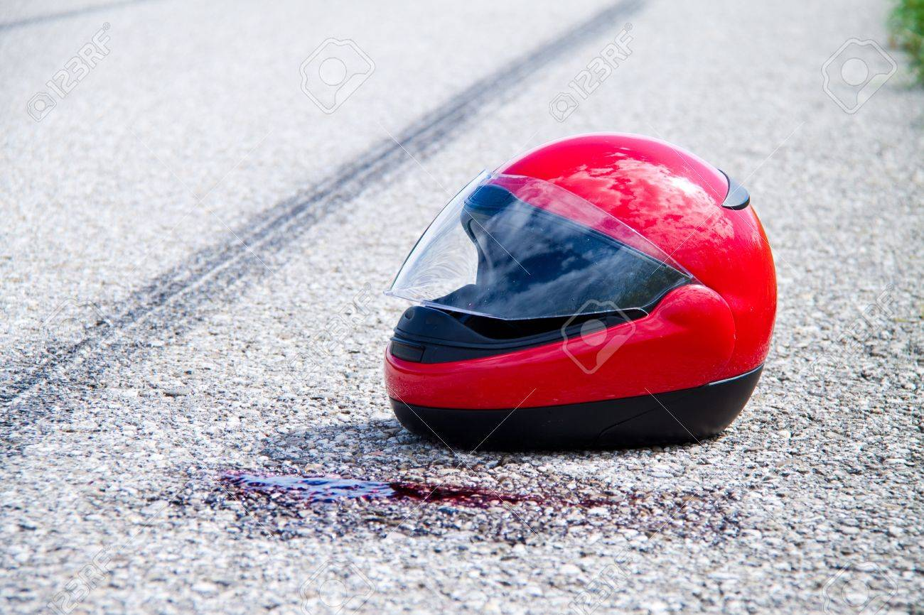 motorcycle helmet with some blood stains on the road Stock Photo - 16354699