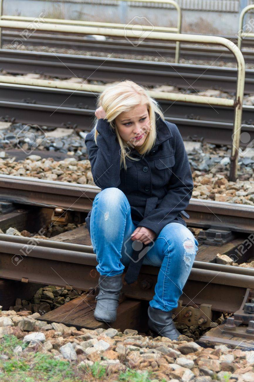 a young woman is sad, anxious and depressed  sitting on a track and is lonely Stock Photo - 16469406