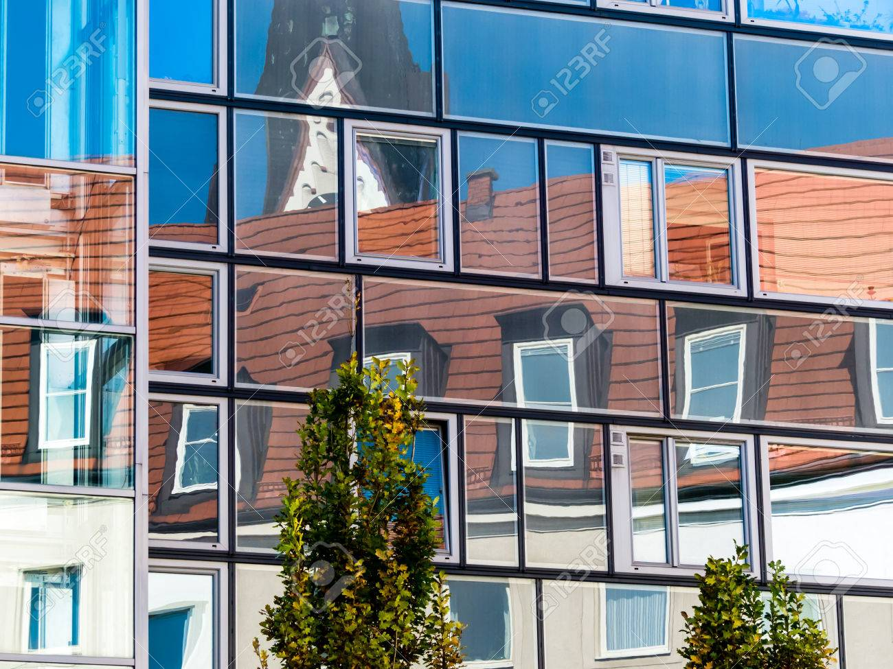 The Roof Extension Of A Residential Building Reflected In The Glass Facade  Of A Modern Office