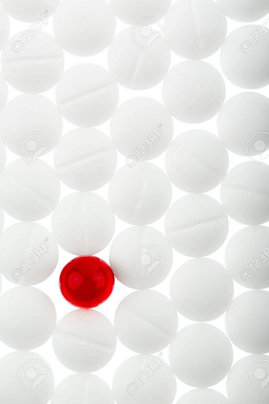 White Tablets In Contrast With A Red Tablet Symbol Photo For
