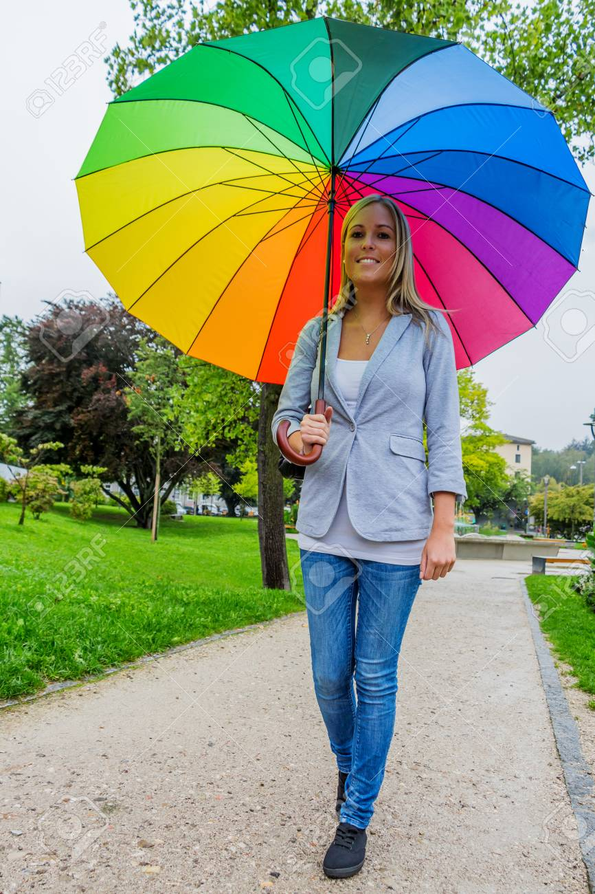 A Young Woman Walks With A Colorful Umbrella In Hand Walking.. Stock ...