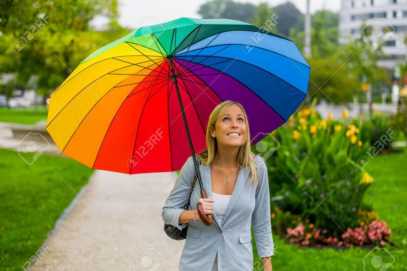 banque dimages une jeune femme marche avec un parapluie color dans la marche de la main sous la pluie - Parapluie Color