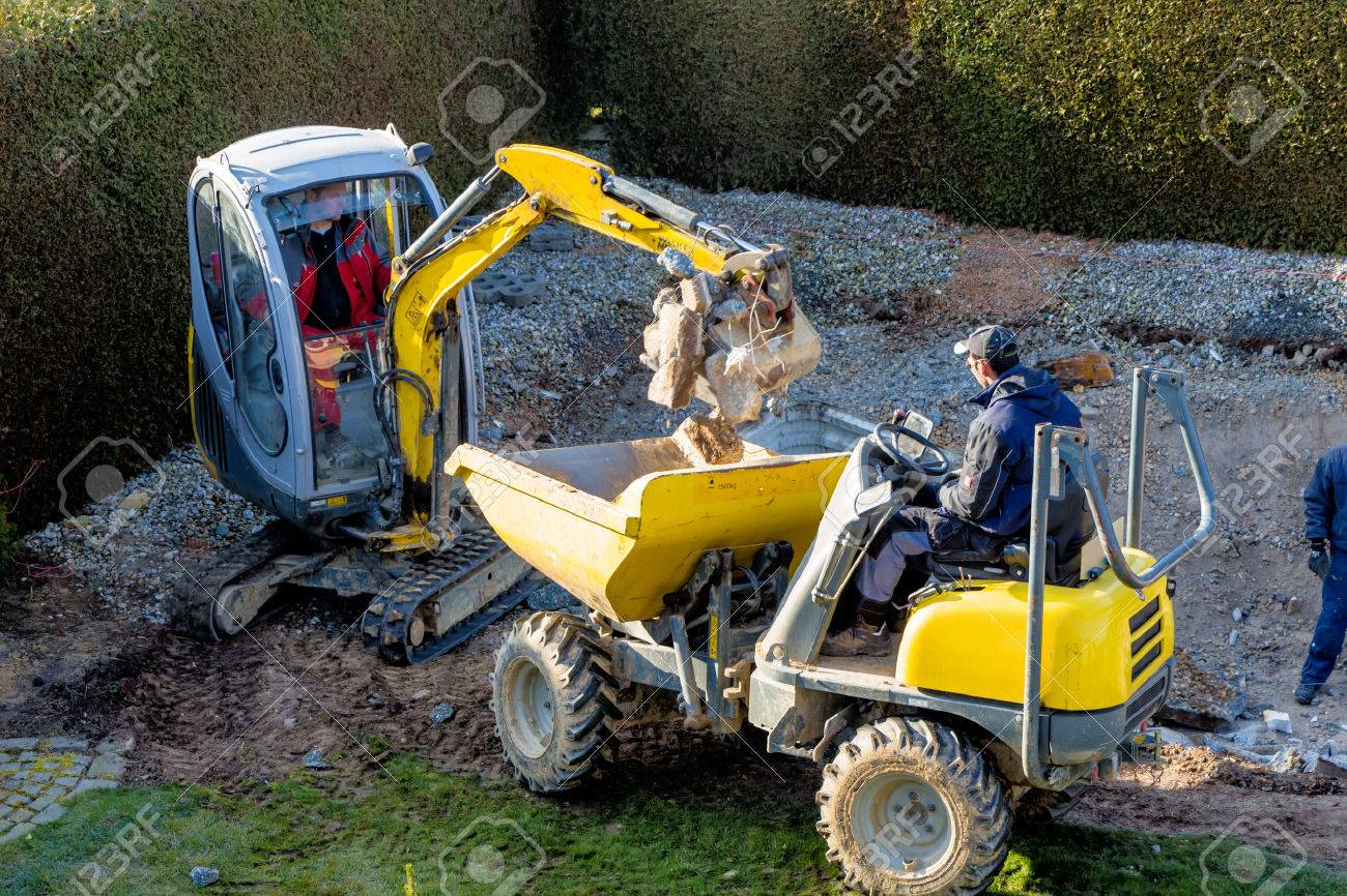 on a private swimming pool construction is dismantled by an excavator Stock Photo - 38260390