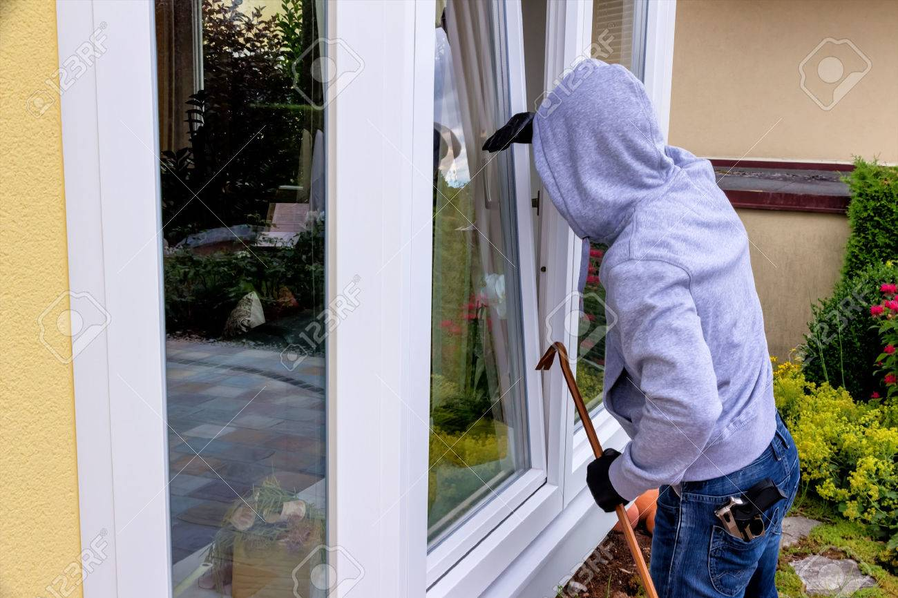 a burglar trying to break in an open window with a crowbar Stock Photo - 38484398