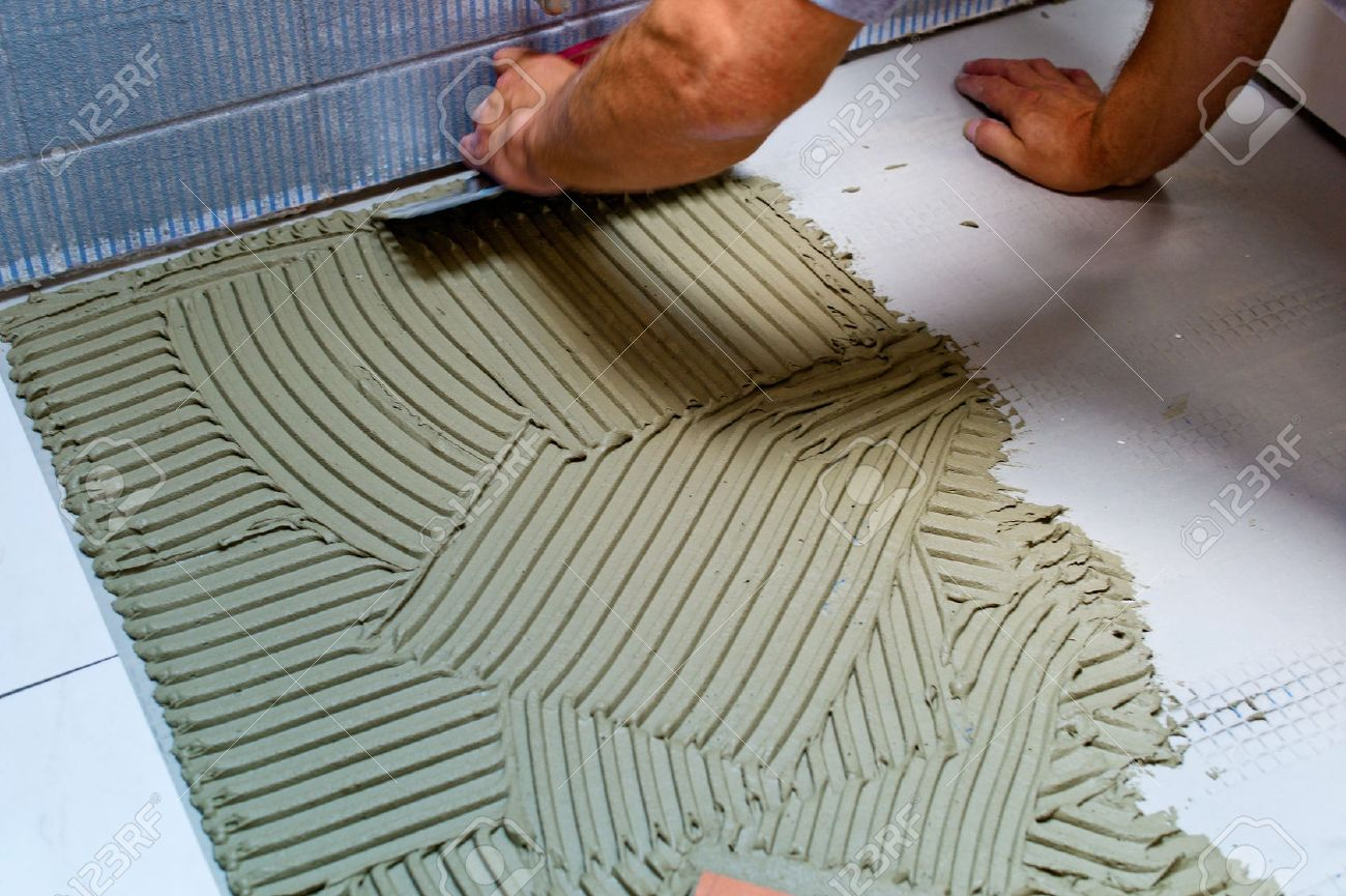 a tiler at work. sticking of floor tiles with tile adhesive and spatula. Stock Photo - 40621850