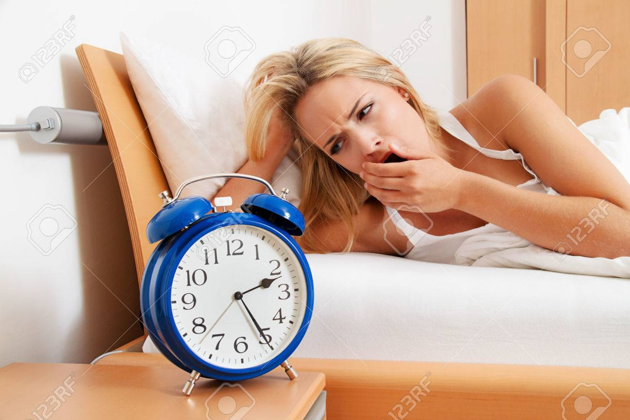 insomnia with clock at night. woman can not sleep. Stock Photo - 44771782