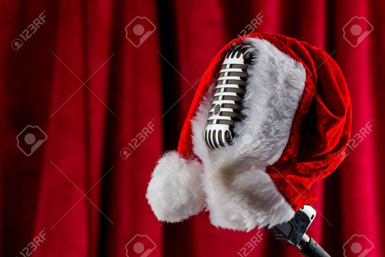 an old retro microphone with santa hat against a red velvet background. Stock Photo - 45704713