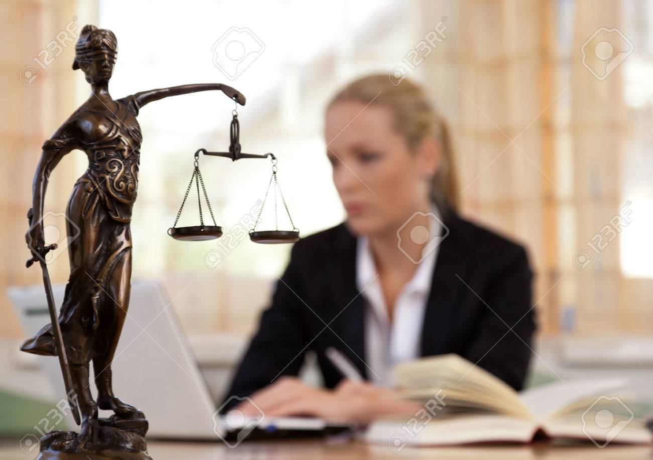 a young lawyer is sitting at her desk in the office - 53973656