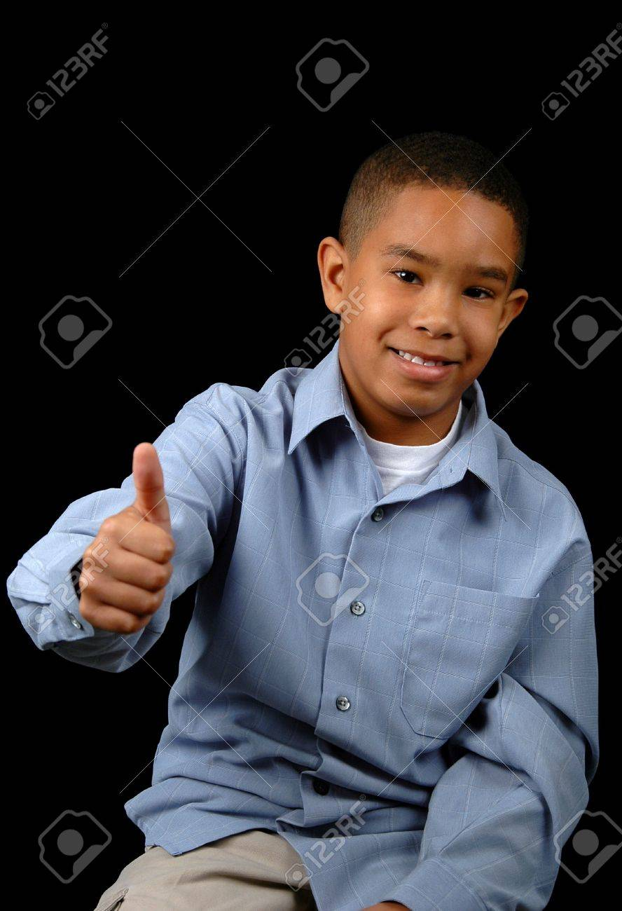 Young boy showing the thumbs-up over a black background. Stock Photo - 897712