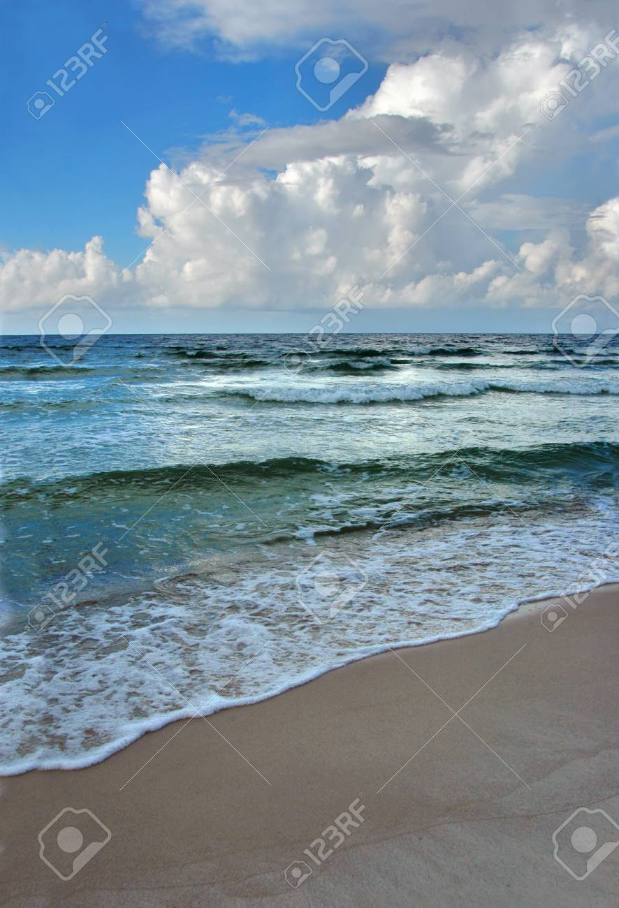 Beach and waves with a pristine and colorful cloud and blue sky background. Stock Photo - 1525410
