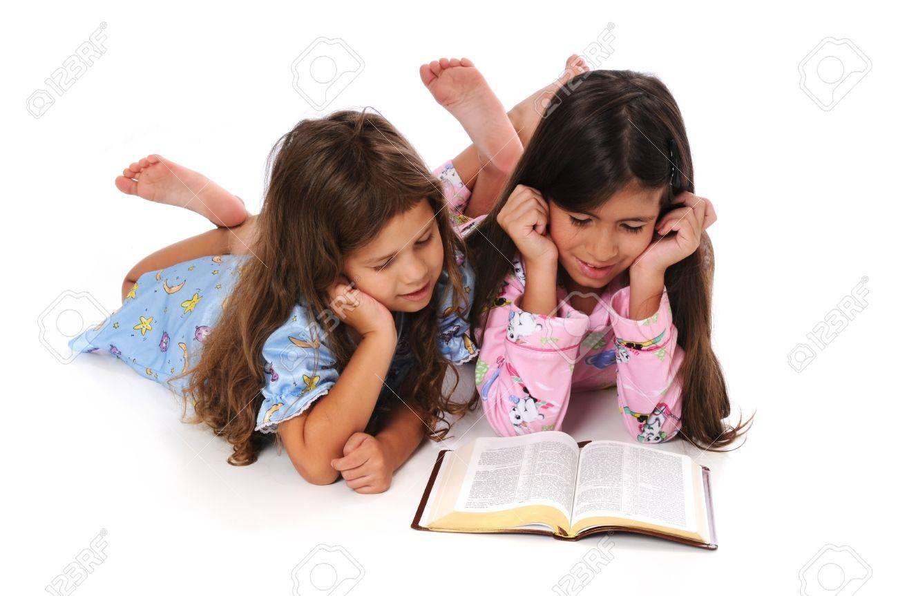 2ebdba29e Young Girls In Pajamas Reading The Bible Before Bedtime Stock Photo ...