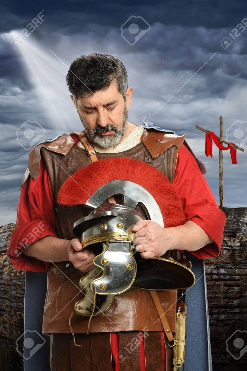portrait of roman soldier praying while holding helmet stock photo