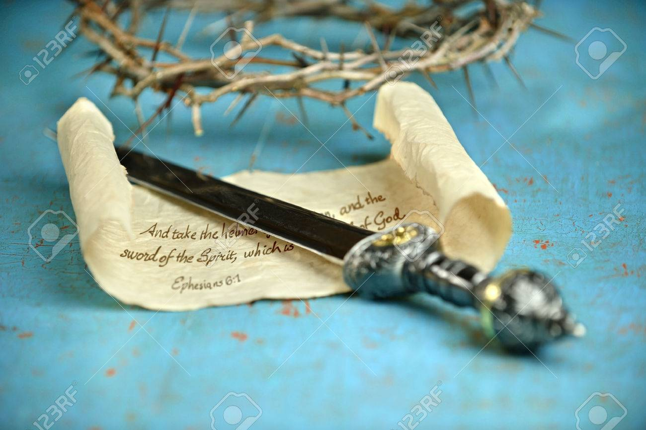 Bible concept of Ephesian 6:1 with sword; scroll; and crown of thorns on vintage table - 31462786