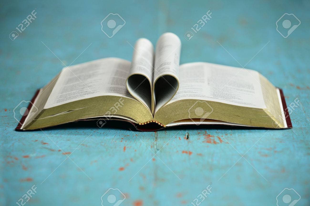 Heart formed by open Bible on vintage table - 32002194