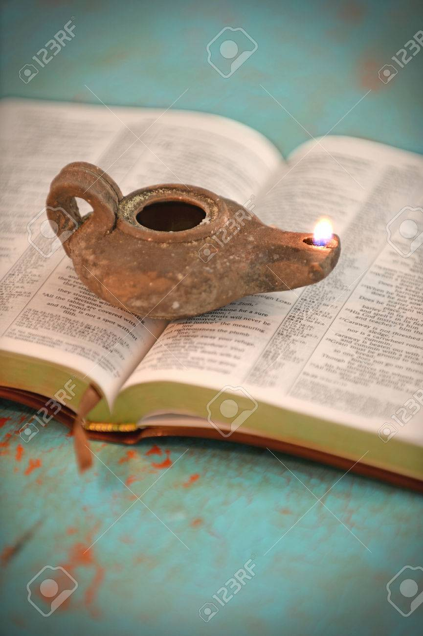 Vintage oil lamp over open Bible on old table - 47647280