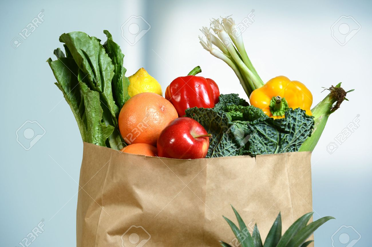 Assortment of fresh produce in grocery paper bag by window - 47647284