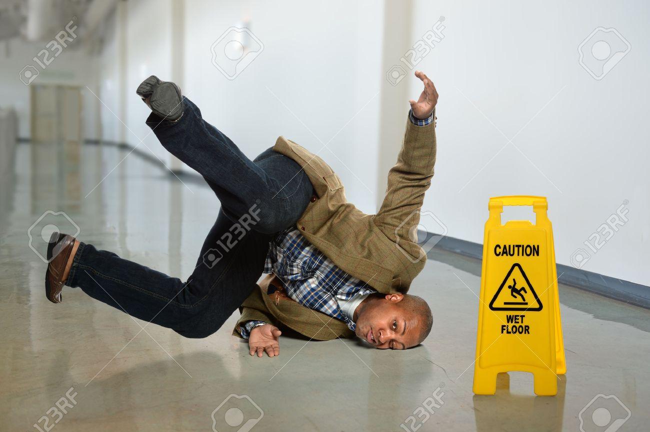 African American businessman falling on wet floor in office - 47035236