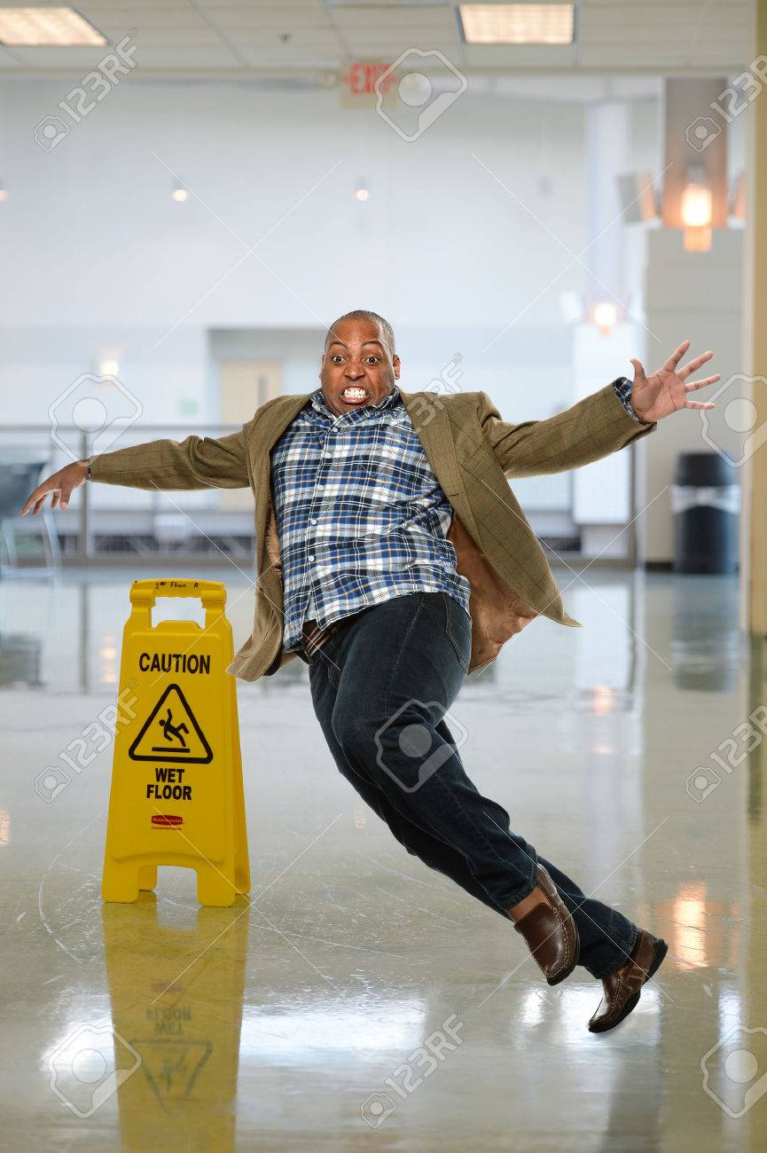 African American businessman slipping on wet floor inside office building - 47035263
