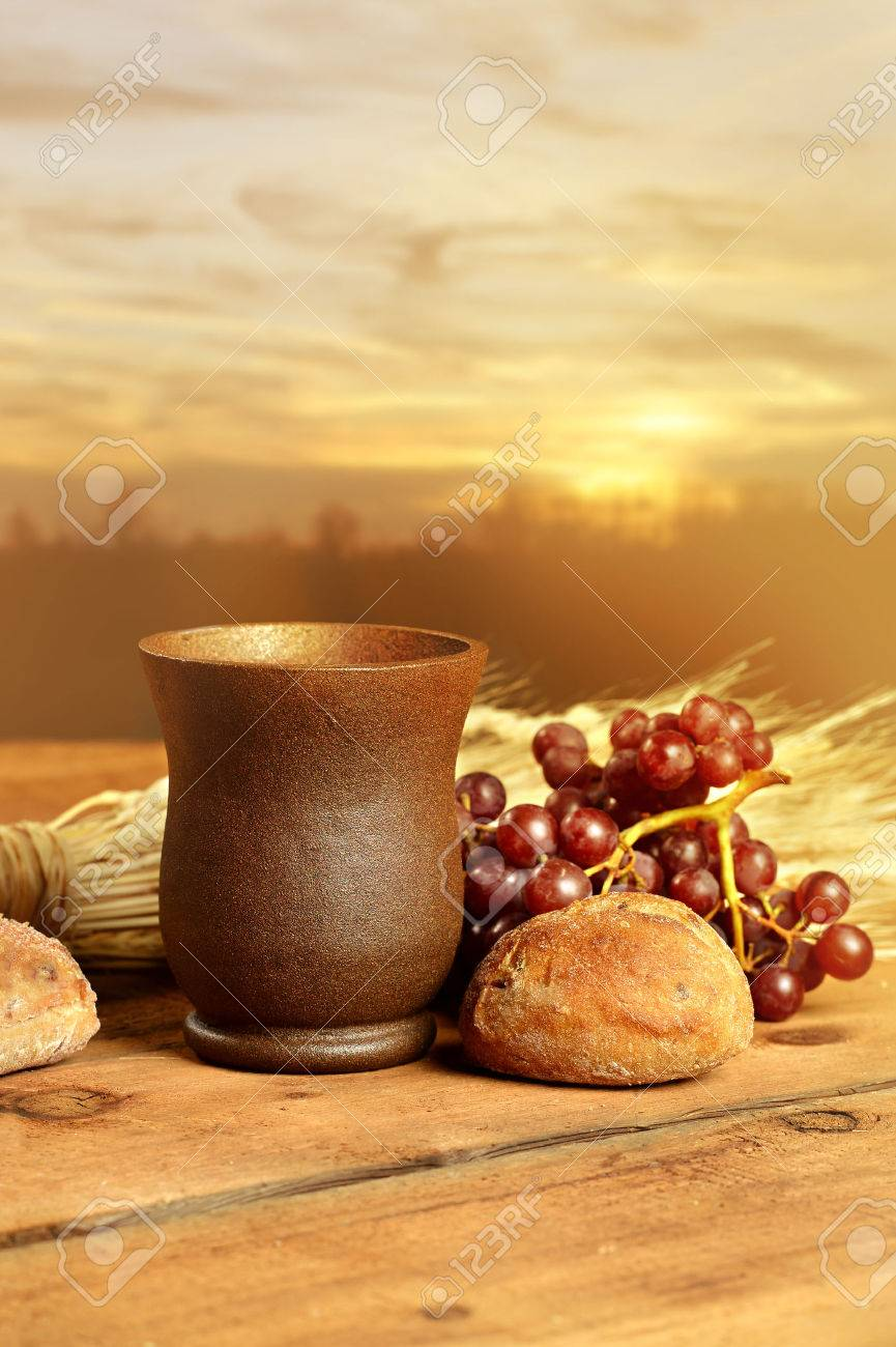 Communion cup with bread, grapes and wheat on wooden table