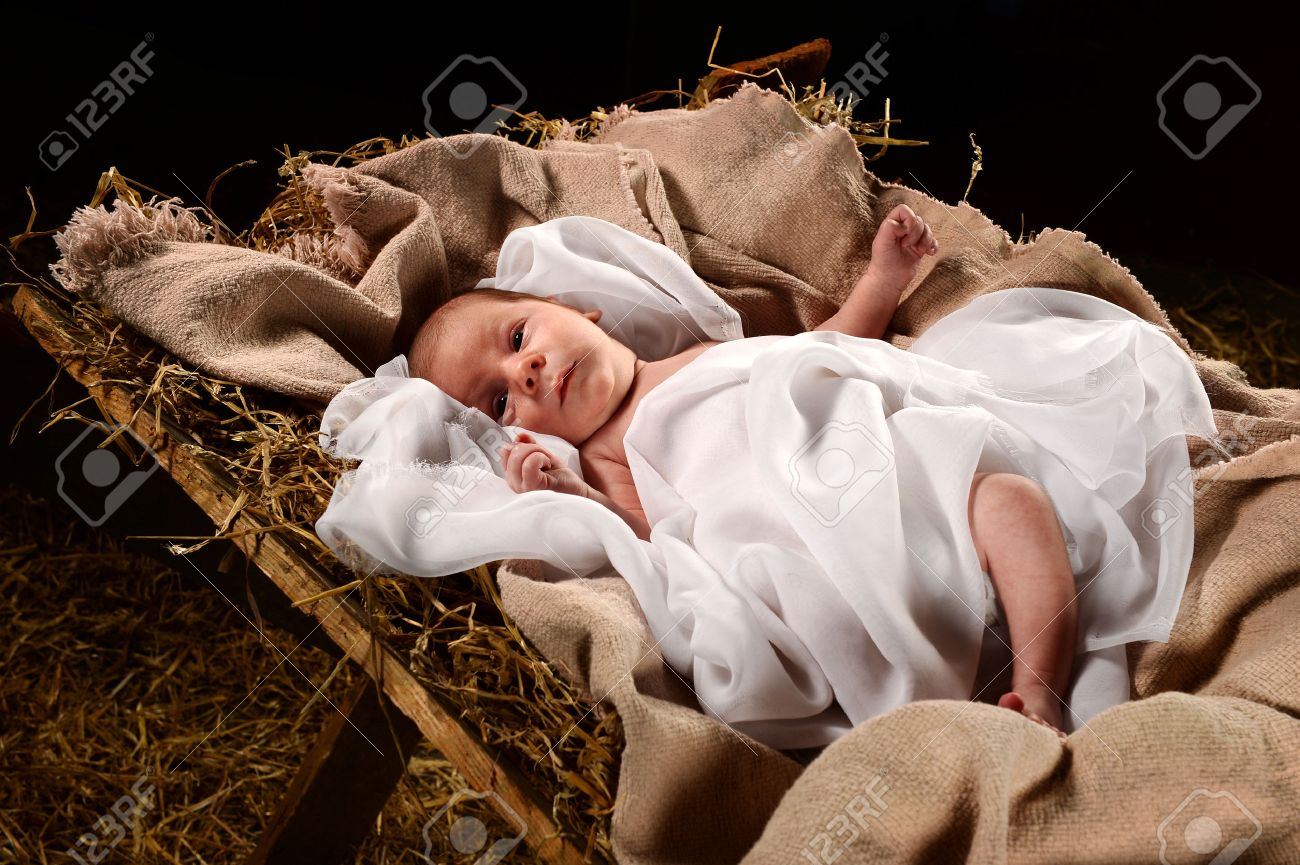 Baby Jesus when born on a manger wrapped in swaddling clothes over dark background - 63773770