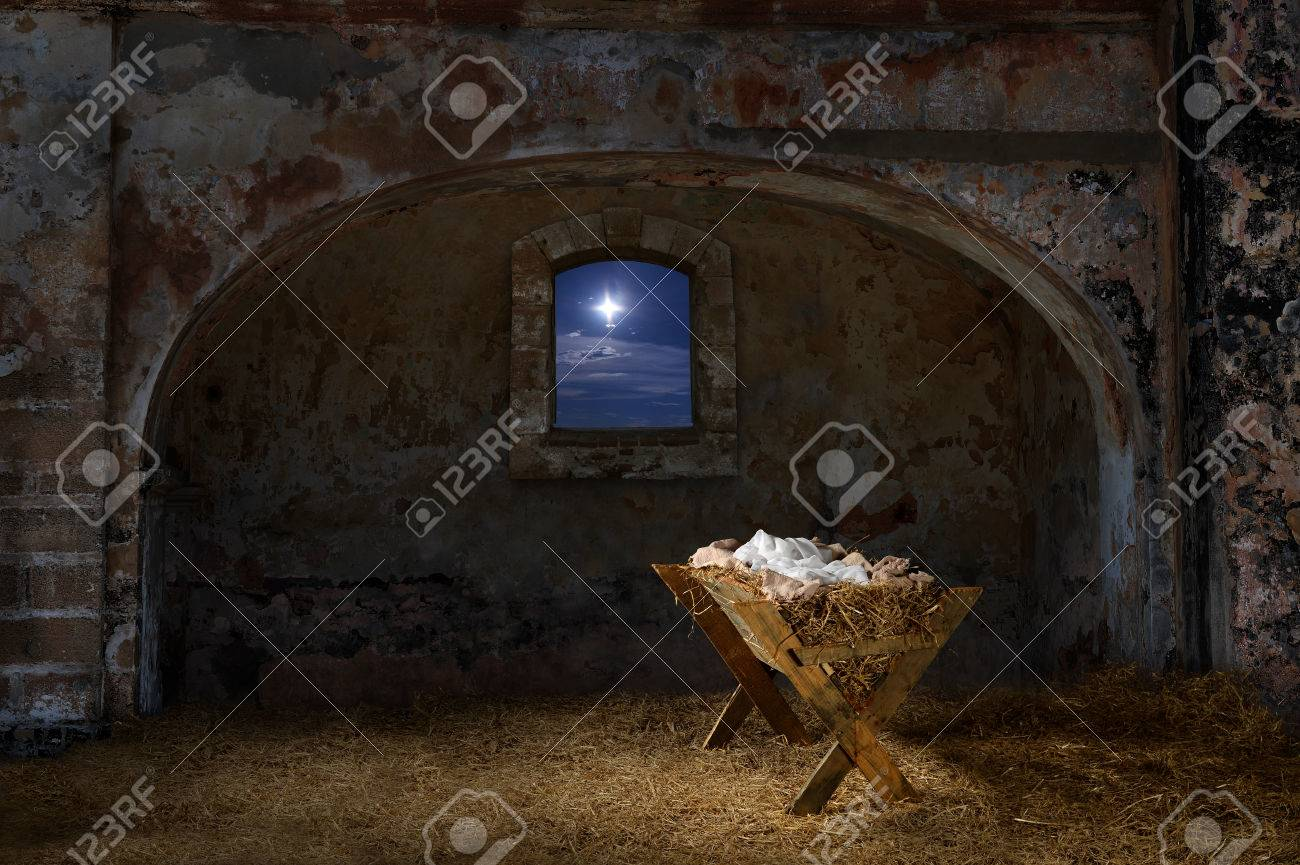 Empty manger in old barn with window showing the Christmas star - 63773857