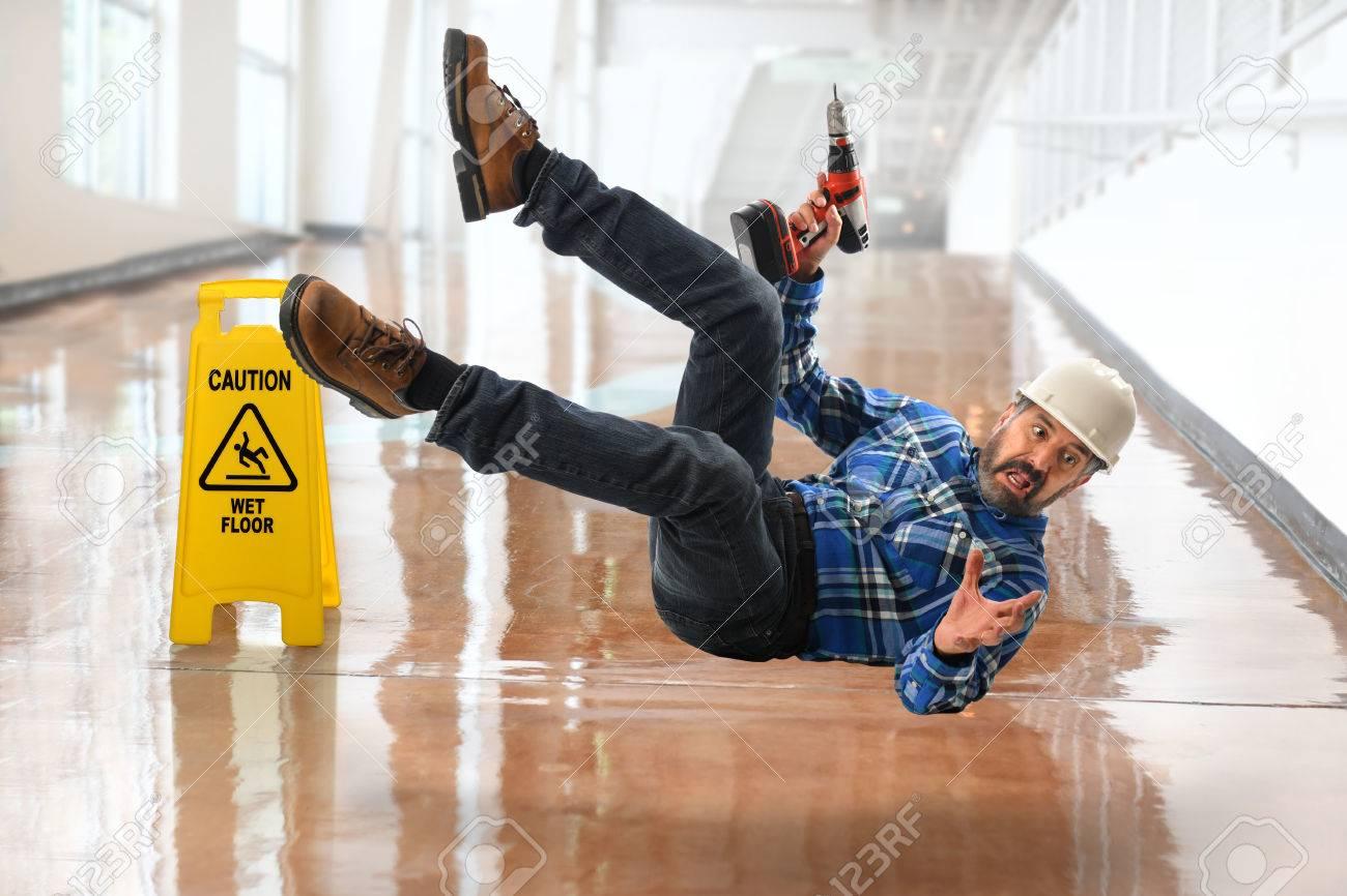 Senior Hispanic worker falling on wet floor - 67035912