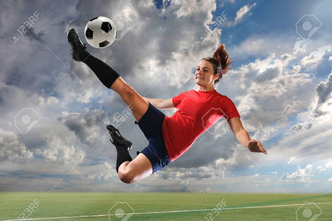Female soccer player kicking ball outdoors - 67035916