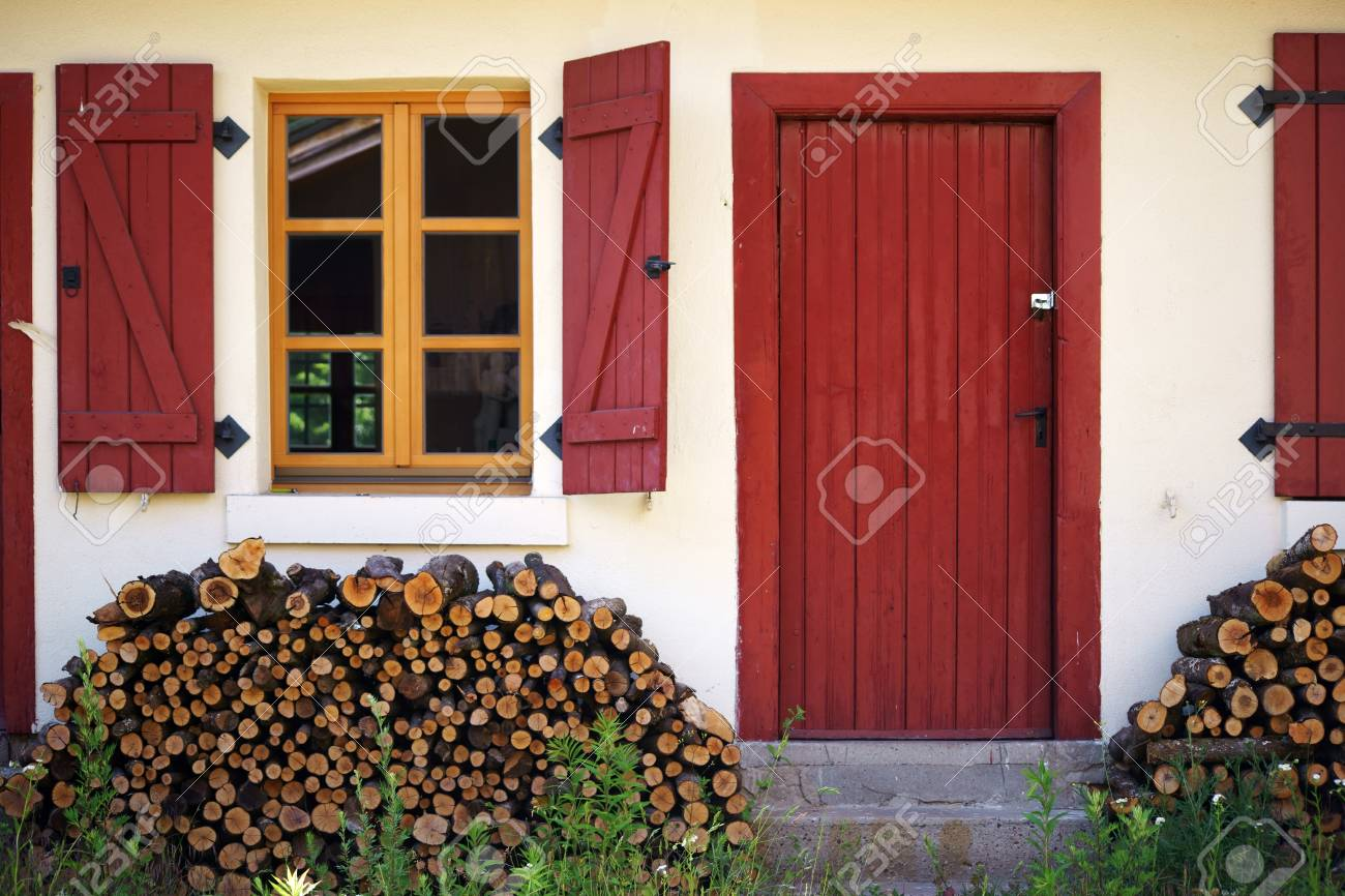 A Hut With Firewood In Front Of The Entrance Door And Window Stock