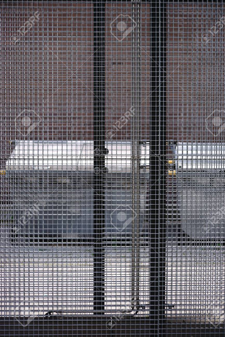 waste containers are behind a grid fence in a lockable outdoor